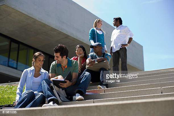 University students socializing and studying on outdoor campus stairs