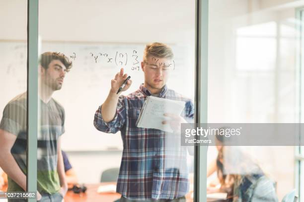 university students solving math problem on a whiteboard - mathematics stock pictures, royalty-free photos & images