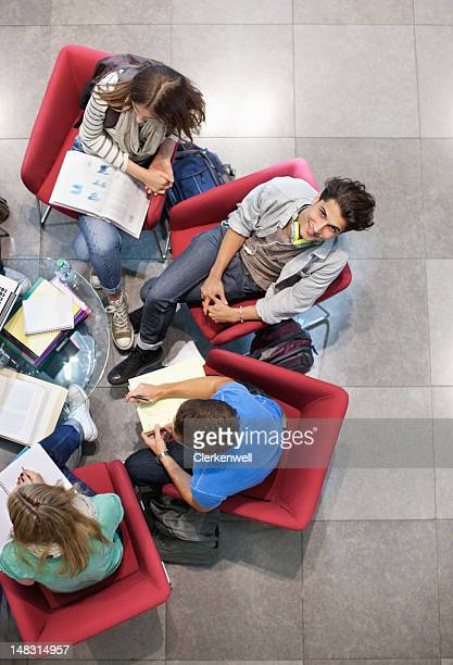 University students studying in armchairs