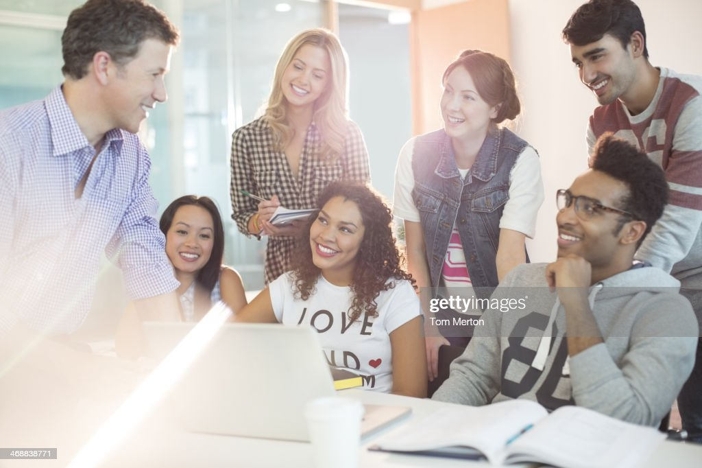 University students talking with teacher in classroom : Stock Photo
