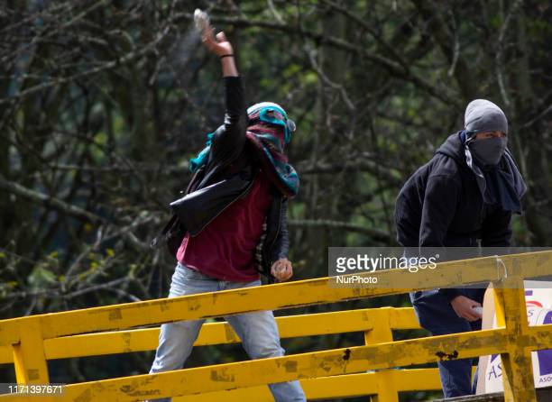 University students throw stones at the police during clashes in Bogota on September 26 2019