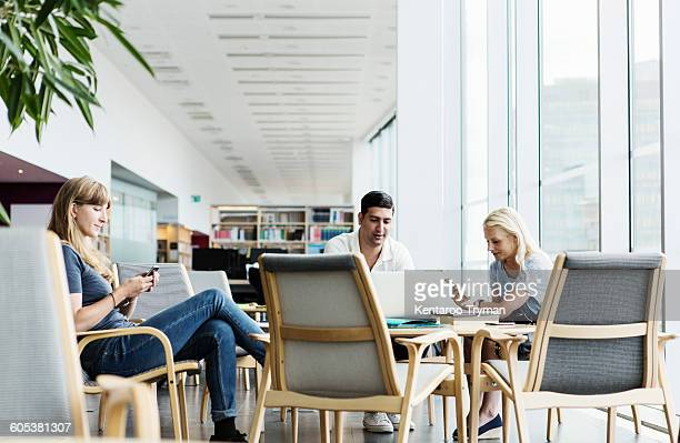 University students using technologies at table in library