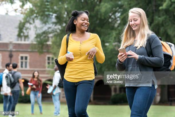 University Students Walking on Campus Using a Mobile Phone