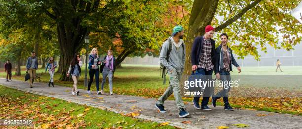 university students walking on footpath - college student stock pictures, royalty-free photos & images