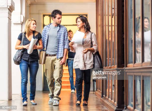 university students walking together through library corridor. - campus stock photos and pictures
