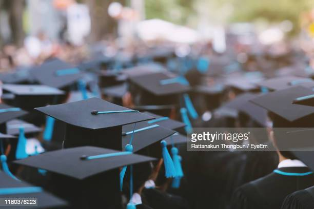 university students wearing graduation gown and mortarboard - graduation stock pictures, royalty-free photos & images