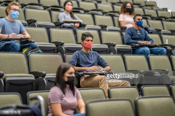 university students wearing masks in a lecture hall - fatcamera stock pictures, royalty-free photos & images
