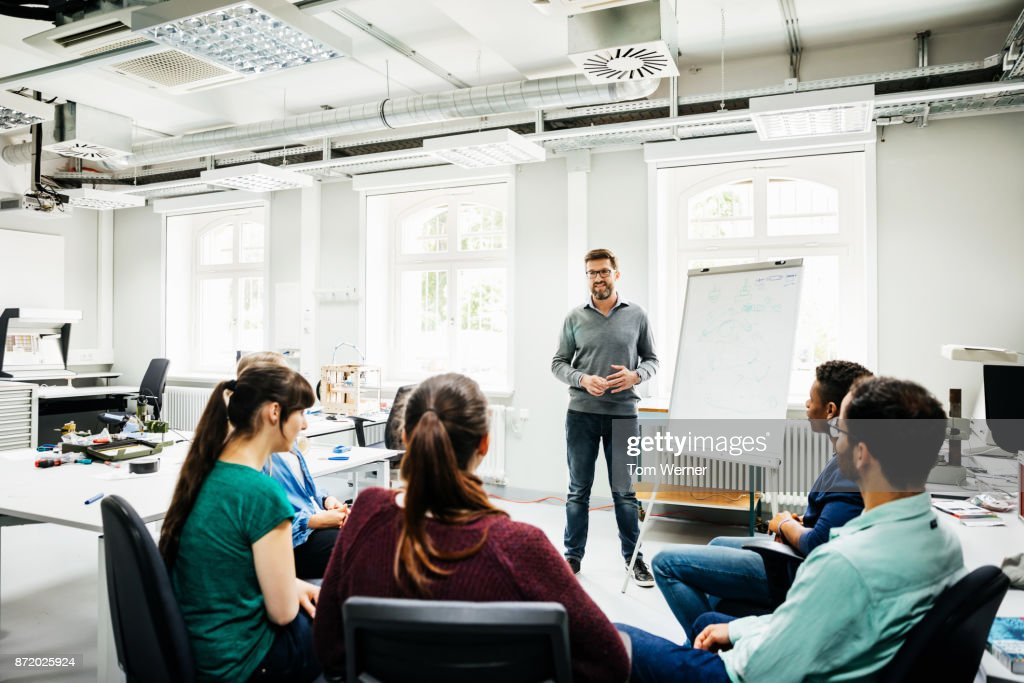 University Tutor Speaking To Students During Seminar : Stock Photo