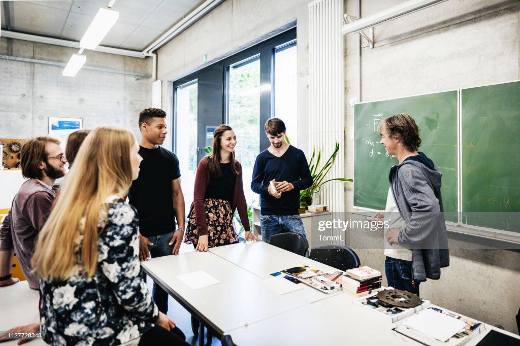 Universität Tutor im Gespräch mit Studenten vor Blackbaord : Stock-Foto