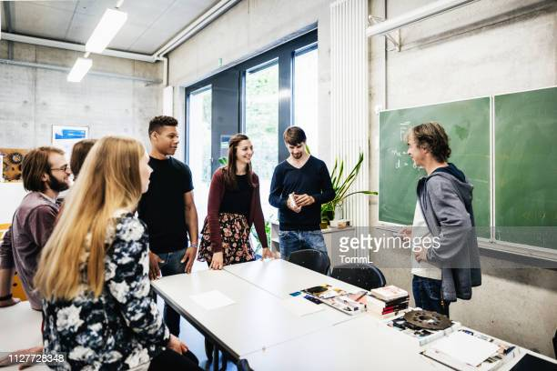 university tutor talking with students in front of blackbaord - demonstration stock pictures, royalty-free photos & images