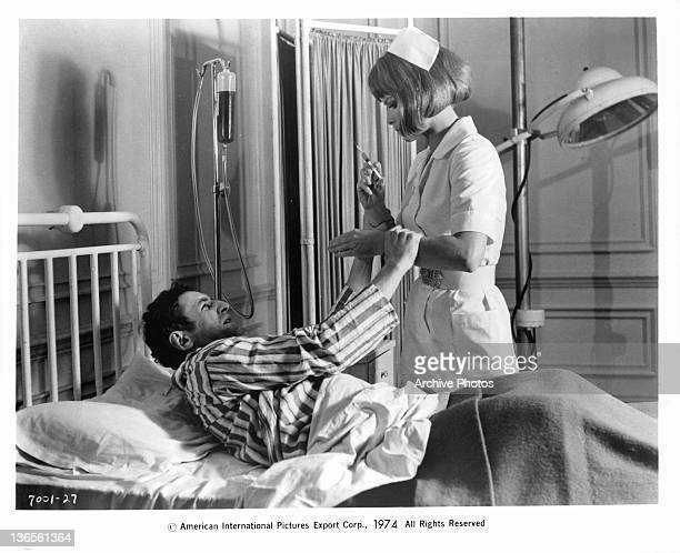 Unknown actor lying in a hospital bed pushing a nurse away who has a needle in her hand in a scene from the film 'ScreamScream Again' 1970