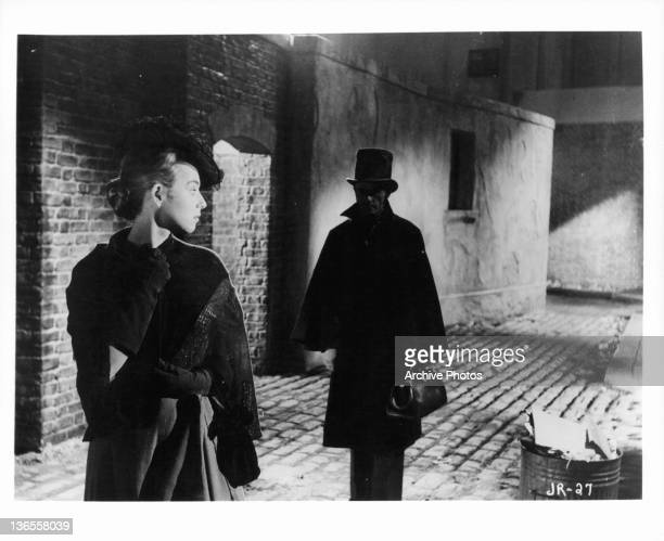 Unknown actress looking back at a man following her in a scene from the film 'Jack The Ripper', 1959.
