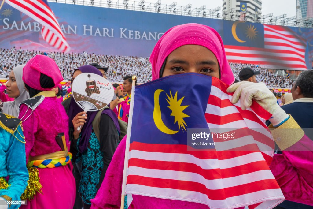 Unknown girl behind national flag of Malaysia. : Stock Photo