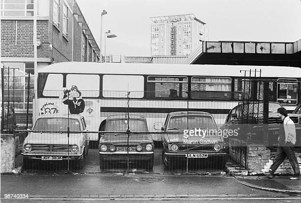 Unknown man walking past a used car lot in Brixton with three cars and a coach January 1988