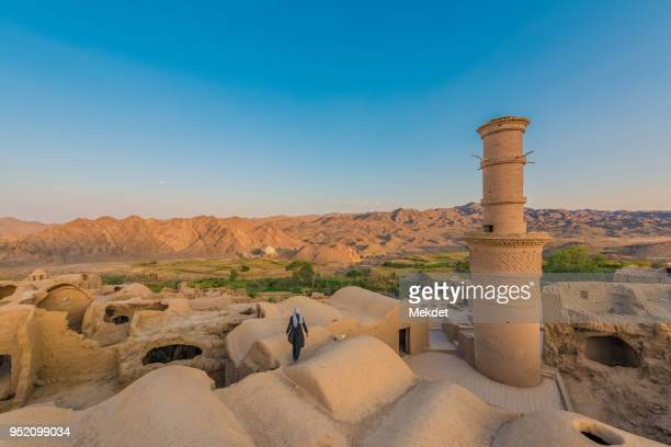 unknown tourist at the adobe, mud and brick ancient village of kharanaq, yazd province, iran - iran stock pictures, royalty-free photos & images
