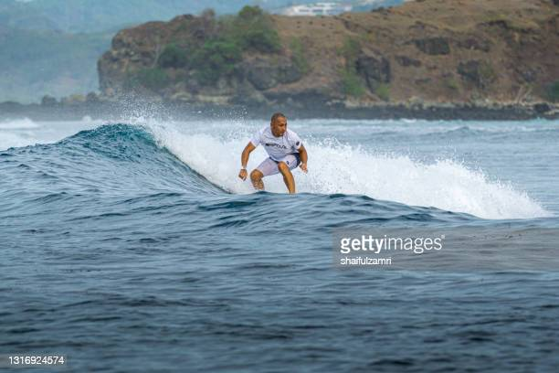 unknown tourist enjoying surfing activities in lombok island - shaifulzamri stock pictures, royalty-free photos & images