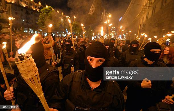 """Unknown ultra-nationalists activists march towards the Independence Square to commemorate """"Maidan heroes"""" in Kiev on April 29, 2014. AFP PHOTO/..."""