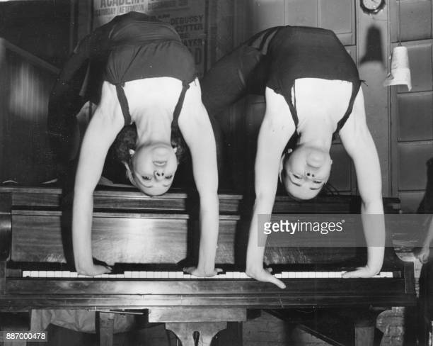 Unlocated picture released on December 10 1938 of young acrobat girls providing entertainment on a piano / AFP PHOTO /