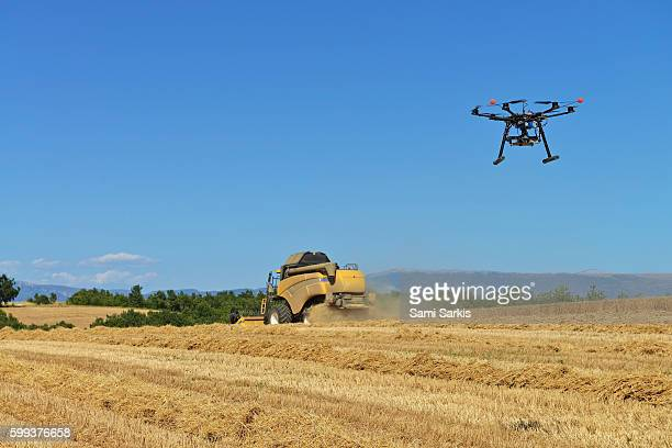 Unmanned Aerial Vehicle (UAV) filming a combine harvester in wheat field in summer in Valensole, Provence-Alpes-Cote d'Azur, France, Europe