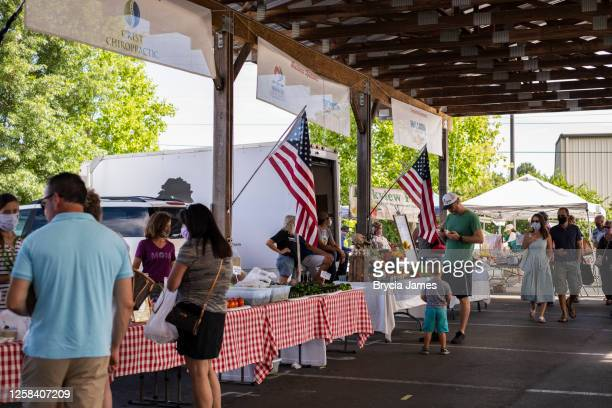 unmasked man among masked shoppers at the farmers market - brycia james stock pictures, royalty-free photos & images