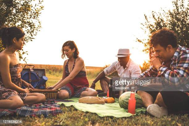 unpacking the picnic basket to enjoy time with friends - mexican picnic stock pictures, royalty-free photos & images