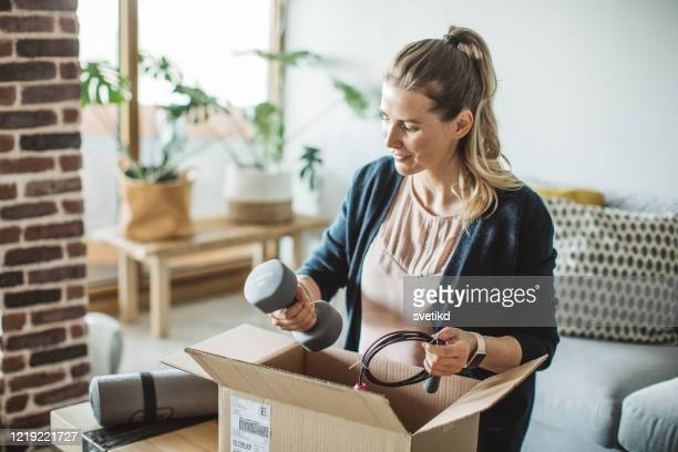 unpacking workout equipment delivery in pandemic situation - sports equipment stock pictures, royalty-free photos & images