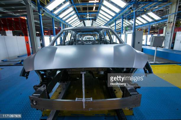 Unpainted Ford Focus automobile bodies sit inside a light tunnel at the Ford Motor Co. Factory in Saarlouis, Germany, on Wednesday, Sept. 25, 2019....