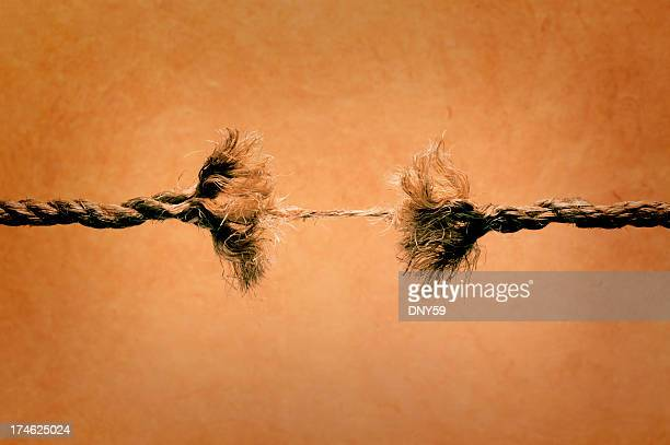 Unraveling rope about to break against brown background