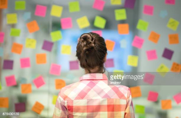 Unrecoginzable woman at the office thinking ideas for the business using adhesive notes