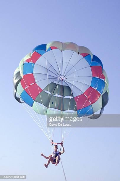 Unrecognisable adult jumping parachute, low angle