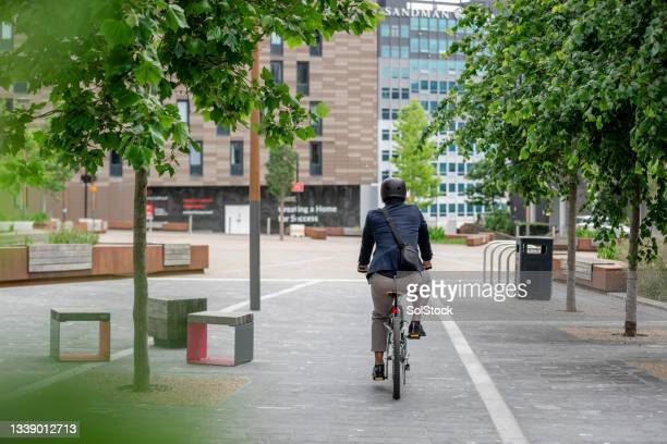 unrecognisable businessman cycling in the city - green blazer stock pictures, royalty-free photos & images