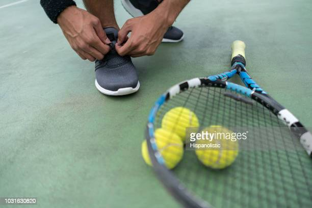 unrecognisable man tying his shoe next to his racket and tennis balls - tennis player stock pictures, royalty-free photos & images
