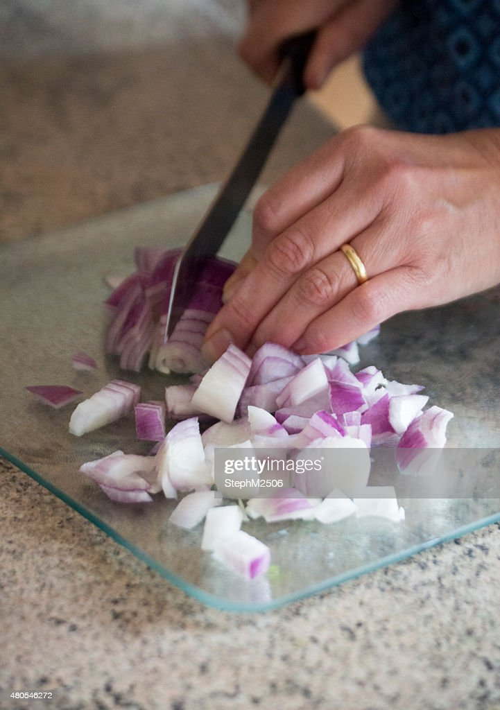 Unrecognisable woman chopping a red onion on a chopping board : Stock Photo