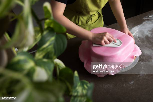 unrecognisable woman in bakery decorating heart shaped wedding cake with pink fondant, view from... - andrea joy cook stock pictures, royalty-free photos & images