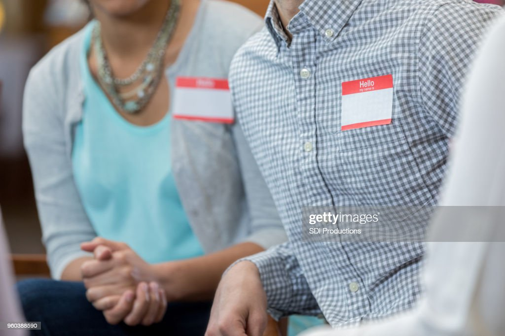 unrecognizable adults with name tags during meeting stock photo