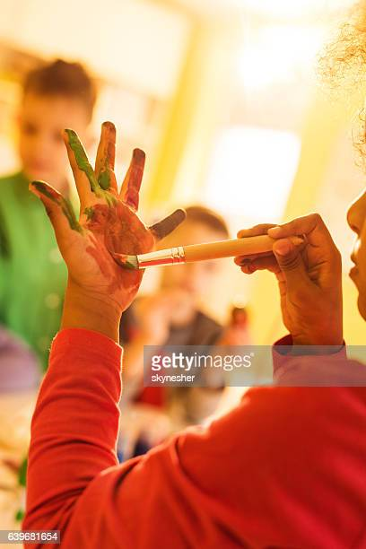 Unrecognizable African American girl coloring her hands with paintbrush.