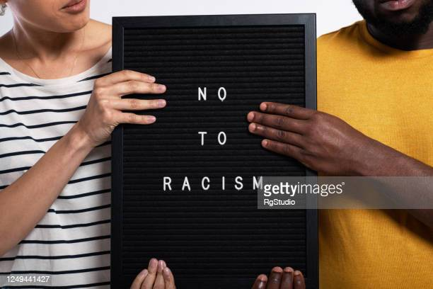 """unrecognizable african-american couple posing in a studio with a sign """"no to racism"""" - racism stock pictures, royalty-free photos & images"""