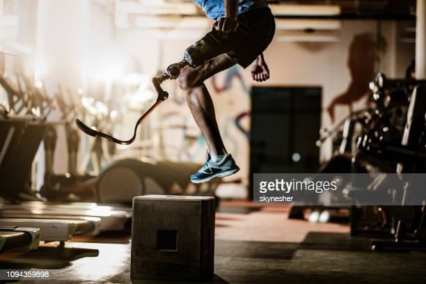 Unrecognizable amputee jumping on crate during cross training in a gym.