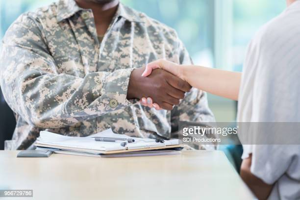 unrecognizable army recruitment officer greets potential recruit - veterans stock photos and pictures