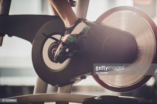 unrecognizable athlete having a exercising class on stationary bike in a gym. - exercise bike stock photos and pictures