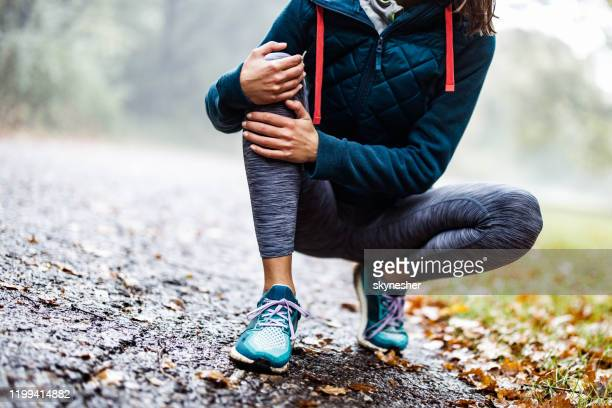 unrecognizable athlete holding her knee in pain at the park. - pain stock pictures, royalty-free photos & images