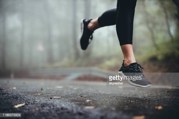 unrecognizable athlete jogging on the road during rainy day. - sports shoe stock pictures, royalty-free photos & images