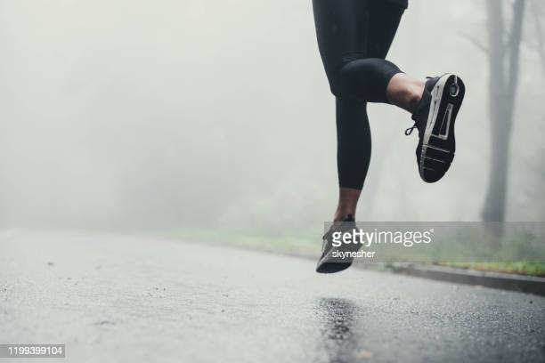 unrecognizable athlete jogging on the road during rainy day. - black shoe stock pictures, royalty-free photos & images