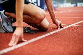 Unrecognizable Athlete Preparing For Start On Running Track.