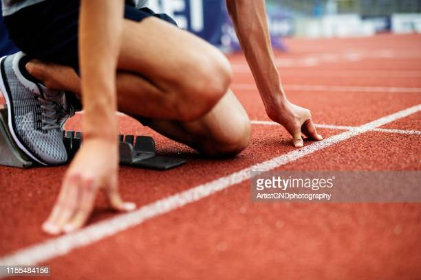 unrecognizable athlete preparing for start on running track. - beginnings stock pictures, royalty-free photos & images