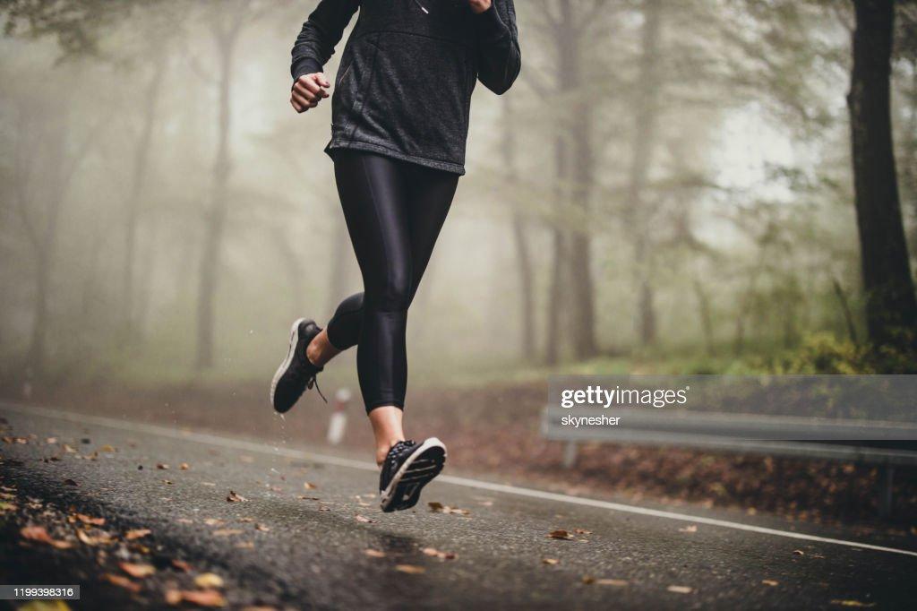 Onherkenbaar atleet draait op Misty Autumn Day in het bos. : Stockfoto