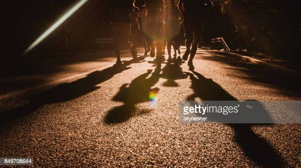 Unrecognizable athletes running a marathon race on the road at sunset.