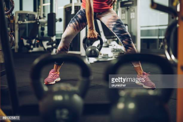 Nicht erkennbare sportliche Frau mit Wasserkocher Glocke in einem Fitnessstudio trainieren.
