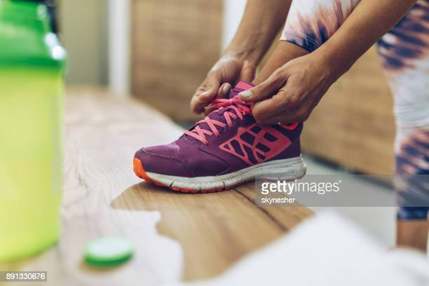 unrecognizable athletic woman tying shoelaces in dressing room. - shoelace stock pictures, royalty-free photos & images