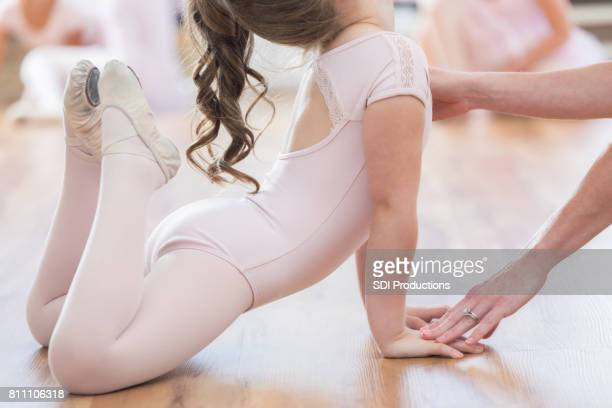 unrecognizable ballerina receives assistance with floor pose - little girls dressed up wearing pantyhose stock photos and pictures